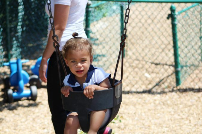 2-year-old_girl_in_swing_at_cadence_academy_preschool_lexington_sc-675x450
