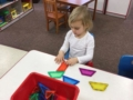 2-year-old_girl_playing_with_colored_parallelograms_cadence_academy_preschool_westerly_ri-600x450