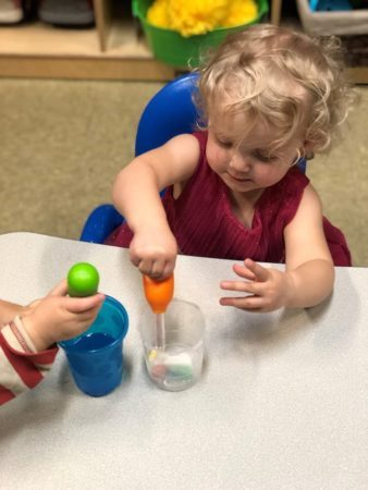 2-year-old_girl_playing_with_eye_dropper_cadence_academy_preschool_sellwood_portland_or-338x450