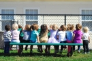 2-year-olds_sitting_on_bench_on_playground-673x450