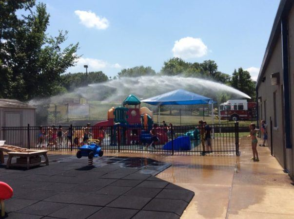 fire_department_fire_hose_cooling_off_children_on_playground_creative_expressions_learning_center_eureka_mo-603x450