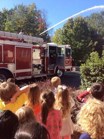 fire_man_demonstrating_hose_at_gateway_academy_mckee_charlotte_nc-336x450