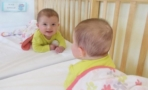 infant_smiling_into_mirror_cadence_academy_preschool_wilmington_nc-741x450