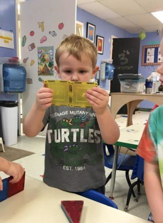 preschool_boy_attaching_magnetic_squares_cadence_academy_preschool_grand_west_des_moines_ia-329x450