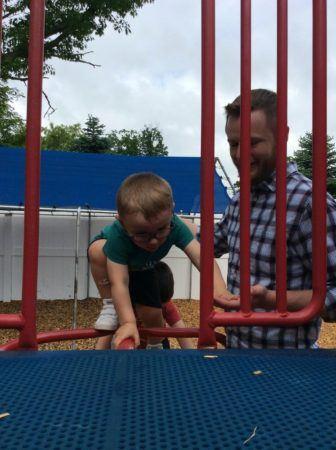 preschool_boy_climbing_onto_playground_structure_next_generation_childrens_centers_westford_ma-336x450