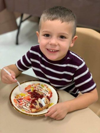 preschool_boy_eating_pie_at_thanksgiving_dinner_cadence_academy_preschool_steele_creek_charlotte_nc-338x450