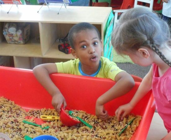 preschool_boy_playing_in_pasta_tub_prime_time_early_learning_centers_edgewater_nj-550x450