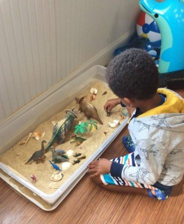 preschool_boy_playing_in_sand_with_dinosaurs_winwood_childrens_center_ashburn_va-370x450