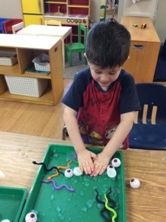 preschool_boy_playing_with_ice_snakes_and_eyeballs_next_generation_childrens_centers_natick_ma-336x450