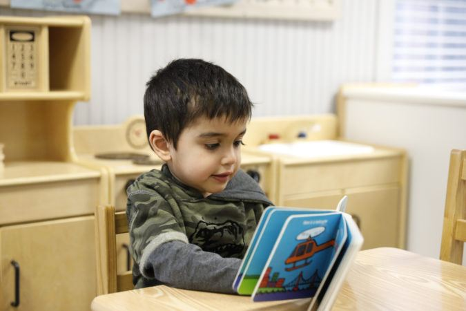 preschool_boy_reading_book_at_table_winwood_childrens_center_leesburg_va-675x450