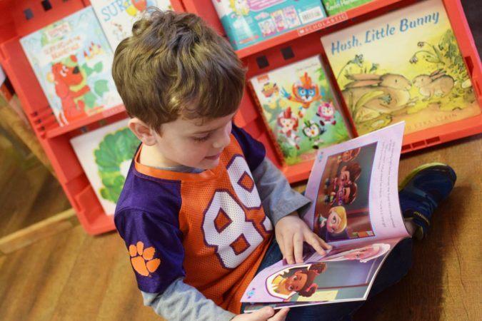 preschool_boy_reading_book_during_scholastic_book_fair_cadence_academy_preschool_mauldin_sc-675x450