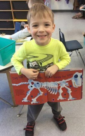 preschool_boy_showing_off_dinosaur_book_adventures_in_learning_naperville_il-283x450