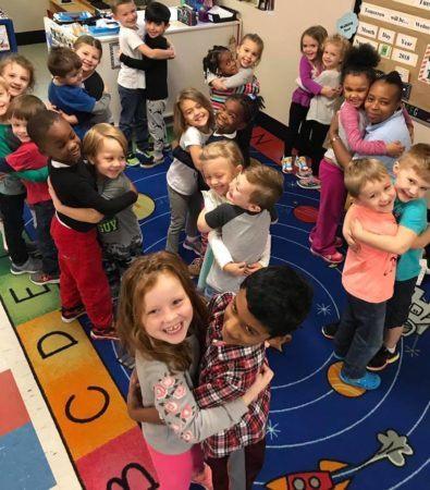 preschool_children_and_teacher_hugging_at_cadence_academy_preschool_summerville_sc-395x450