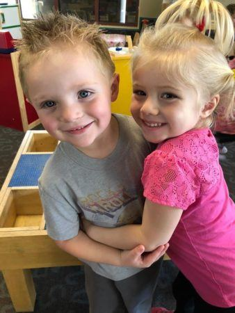 preschool_children_hugging_and_smiling_pusch_ridge_preschool__kindergarten-338x450