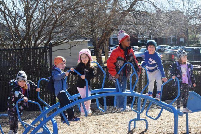 preschool_children_on_stegosaurus_playground_equipment_cadence_academy_preschool_mauldin_sc-675x450