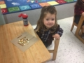 preschool_cowgirl_enjoying_trail_mix_smaller_scholars_montessori_academy_grisby_tx-600x450