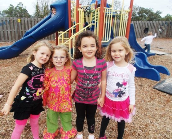 preschool_friends_on_playground_cadence_academy_preschool_wilmington_nc-555x450