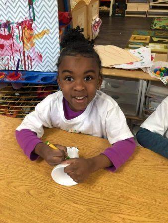 preschool_girl_coloring_on_cup_the_bridge_learning_center_carrollton_ga-338x450
