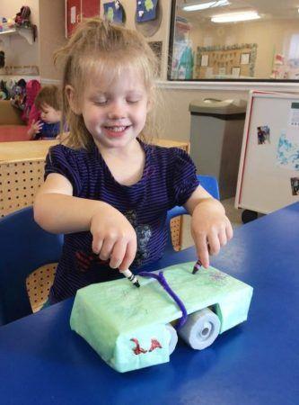 preschool_girl_coloring_with_both_ahands_cadence_academy_preschool_myrtle_beach_sc-333x450