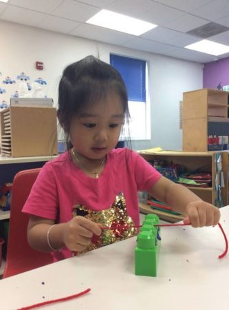preschool_girl_flossing_plastic_block_growing_kids_academy_fredericksburg_va-333x450