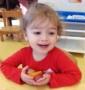 preschool_girl_holding_fruit_carolina_kids_child_development_center_fort_mill_sc-423x450