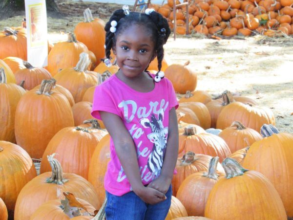 preschool_girl_in_pumpkin_patch_cadence_academy_preschool_harbison_columbia_sc-600x450