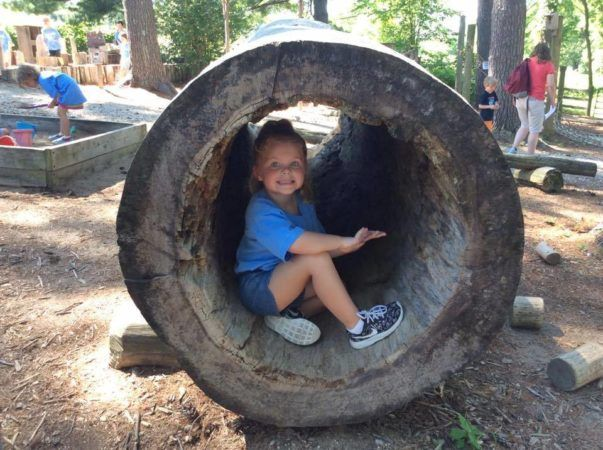preschool_girl_inside_hollowed_out_log_creative_expressions_learning_center_eureka_mo-603x450