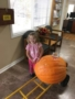 preschool_girl_next_to_giant_pumpkin_miss_muffets_learning_center_klamath_falls_or-338x450