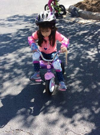 preschool_girl_on_tricycle_with_helmet_and-knee_pads_carolina_kids_child_development_center_rock_hill_sc-333x450