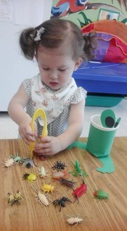preschool_girl_picking_up_plastic_insects_with_tweezers_prime_time_early_learning_centers_edgewater_nj-248x450