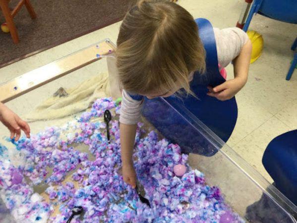 preschool_girl_playing_with_colored_snow_cadence_academy_preschool_westerly_ri-599x450