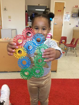 preschool_girl_showing_interlocking_manipulatives_at_cadence_academy_preschool_mallard_charlotte_nc-336x450