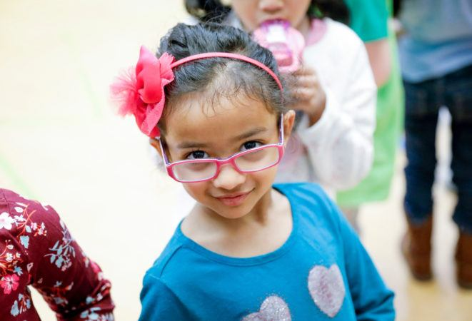 preschool_girl_wearing_glasses_looking_into_camera_winwood_childrens_center_brambleton_va-661x450