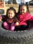 preschool_girls_sitting_in_tire_on_playground_at_cadence_academy_preschool_columbine_littleton_co-333x450