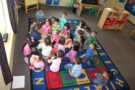 preschool_teacher_and_class_sitting_on_ground_cadence_academy_preschool_san_antonio_tx-675x450