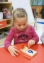 preschooler_doing_peg_activity_cadence_academy_preschool_wilmington_nc-311x450