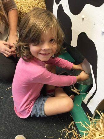 preschooler_learning_how_to_milk_a_cow_winwood_childrens_center_leesburg_va-338x450