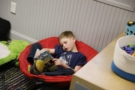 preschooler_reading_book_in_cozy_chair_winwood_childrens_center_leesburg_va-675x450