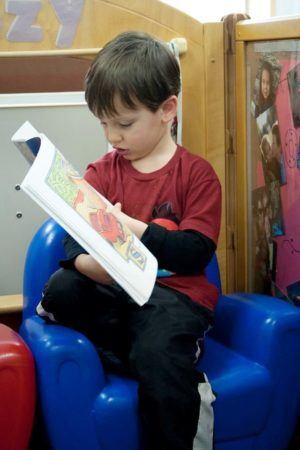 preschooler_reading_book_on_a_soft_chair_cadence_academy_preschool_greensboro_nc-300x450
