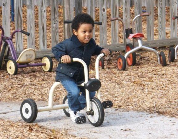 preschooler_riding_tricycle_at_cadence_academy_preschool_summerville_sc-576x450