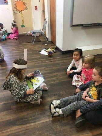 preschoolers_reading_dr_seuss_books_together_childrens_garden_montessori_richland_wa-336x450