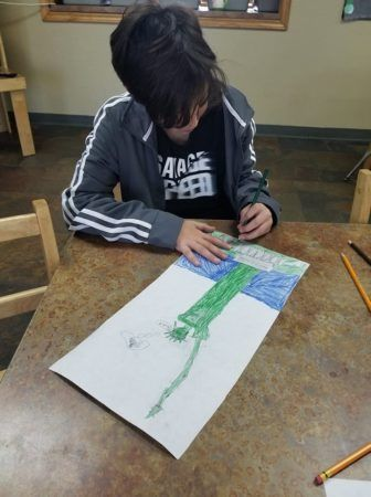 school_age_boy_drawing_the_statue_of_liberty_cadence_academy_preschool_san_antonio_tx-336x450