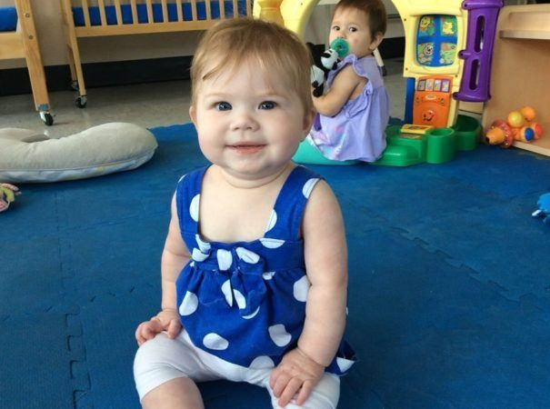 smiling_toddler_sitting_on_padded_blue_floor_cadence_academy_preschool_greenville_sc-605x450