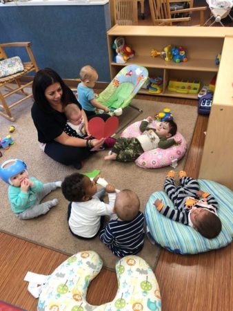 teacher_and_toddlers_sitting_together_on_floor_winwood_childrens_center_ashburn_va-338x450