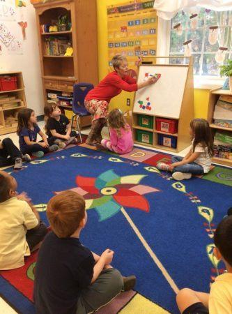 teacher_putting_geometric_shapes_on_whiteboard_winwood_childrens_center_gainesville_ii_va-333x450