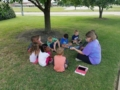 teacher_reading_a_book_outside-600x450