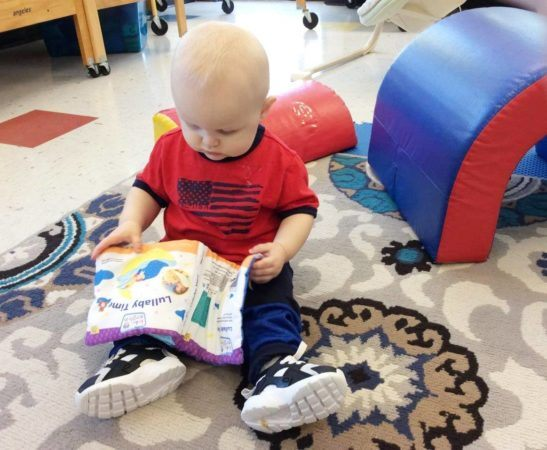 toddler_boy_reading_plush_book_at_cadence_academy_preschool_mount_pleasant_sc-547x450