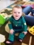 toddler_boy_smiling_and_sitting_on_rug_cadence_academy_preschool_mount_pleasant_sc-338x450