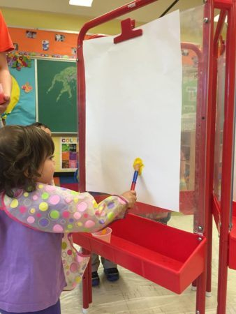 toddler_girl_painting_on_easel_prime_time_early_learning_centers_east_rutherford_nj-338x450