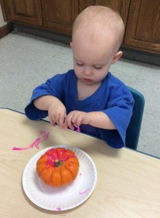 toddler_painting_a_pumpkin_cadence_academy_preschool_urbandale_ia-330x450